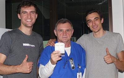 Design for America co-founders and fellows Mert Iseri (left) and Yuri Malina and an intensive-care unit nurse show a prototype of SwipeSense.