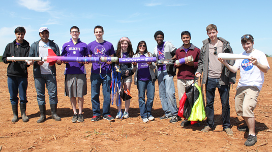 Members of NUSTARS show off pieces of their nine-foot, homemade rocket at NASA's University Student Launch.