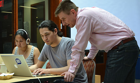 Professor Diego Klabjan (right) observes students participate in the MSiA program's first Hackathon.