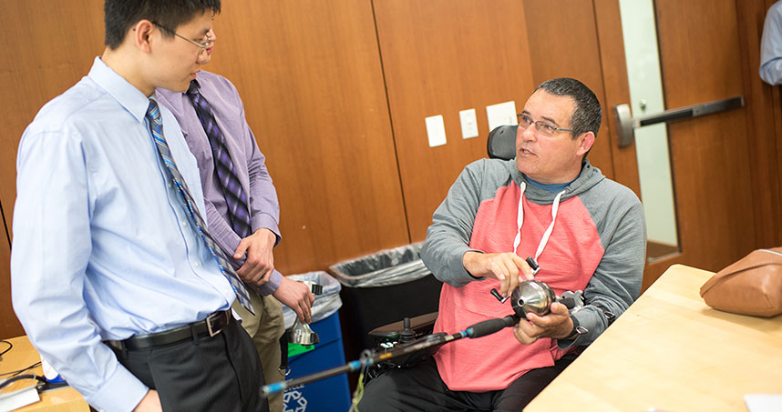 Undergraduate Mathew Li talks to Mike Thompson as he tries out the Bass Grabber.