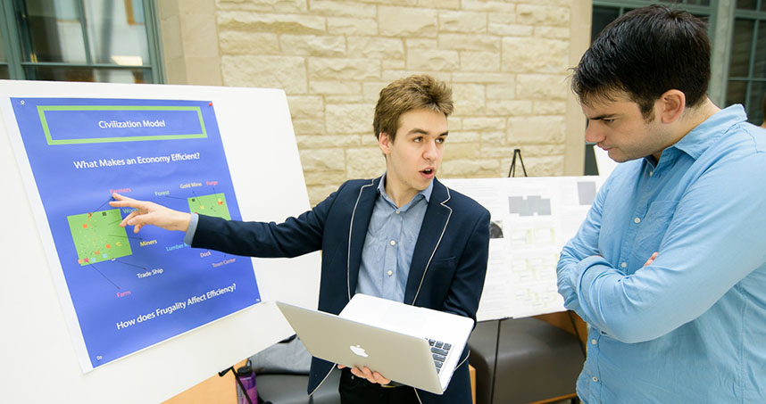 Sophomore Gabriel Pezanoski-Cohen explains his model to a visitor at the poster session.