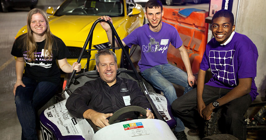 Ford's Joseph Hinrichs sits in the students' Formula racing car.