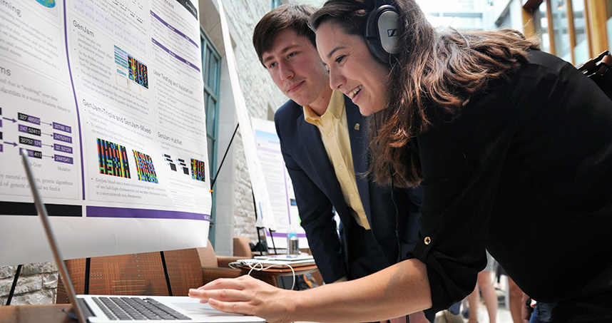 A visitor listens to the music that graduate student Connor Bain (left) composed with NetLogo.