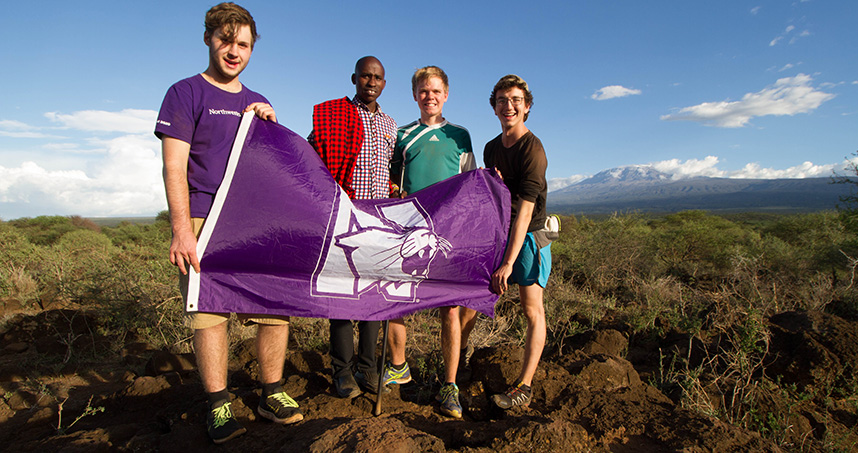EWB-NU students wave a Northwestern flag in front of Mount Kilimanjaro.