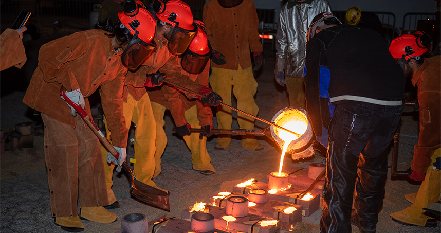 Design 395-64 students pour iron into molds on May 31 in the Ryan Field parking lot. Credit: Rob Hart