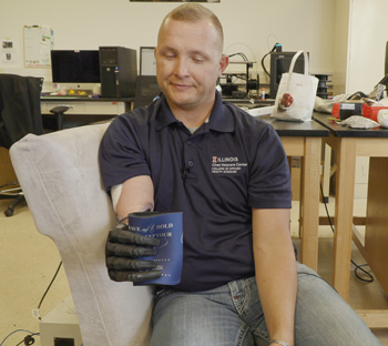 Retired US Army Sgt. Garrett Anderson grabs and grips an object while wearing Northwestern's wireless patch. Credit: Northwestern University